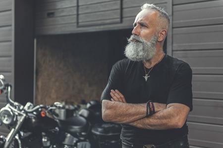 Thoughtful mature bearded man locating near garage