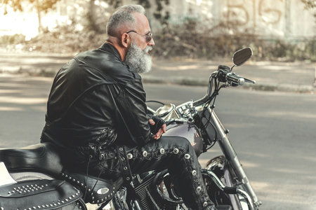 Old male person locating on motorcycle Imagens