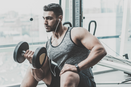 Serene man practicing with equipment in gym