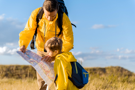 Concentrated father and son reading map during travel Stock Photo