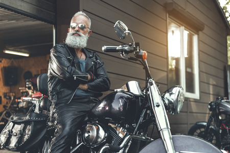 Serious old bearded man on motorcycle