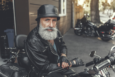 Serious glancing mature man using motorcycle Banco de Imagens