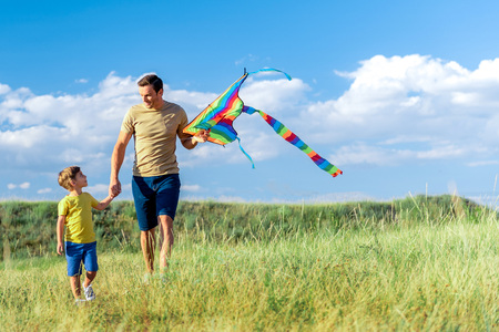 Happy father and son playing with kite in nature