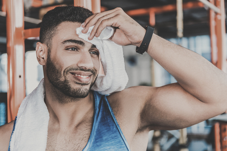 Cheerful unshaven man feeling fatigue after training Stock Photo