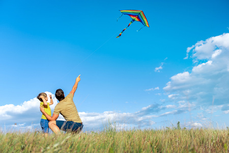 Joyful father and child playing together on grassland Imagens