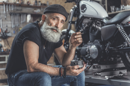 Mindful aged biker is smoking in garage near motorcycle. He using piston as ashtray and looking at camera with wistfulness. Portrait Stok Fotoğraf