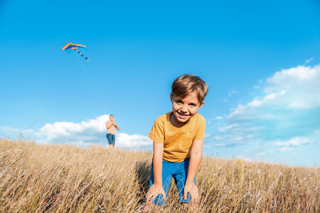 I like playing with my daddy. Low angle portrait of happy boy standing on wheat field. He is looking at camera and laughing. His father is launching a kite on background Reklamní fotografie