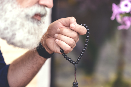 Senior male person calming down himself by counting rosary Imagens - 84430250