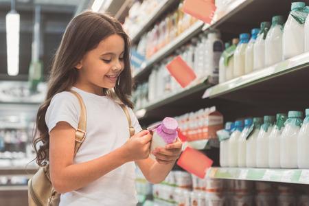 Beaming girl looking at tasty milk