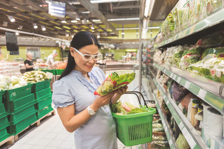 Beaming lady looking through ingredients in supermarkets Imagens - 84499743