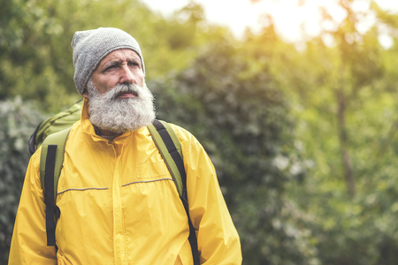 Serious old man traveling in wild nature Reklamní fotografie - 84499746