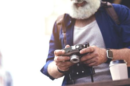 Happy senior male traveler looking at self-made photographs 版權商用圖片