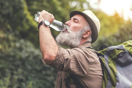 수석 남성 등산객은 매우 목 말라와 마시는 물 스톡 콘텐츠