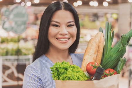 Joyous woman keeping necessary purchases