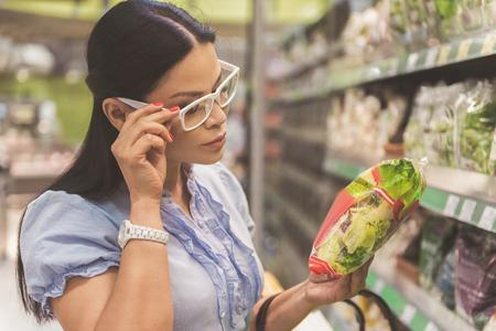 Donna vigile che legge sul prodotto nel negozio