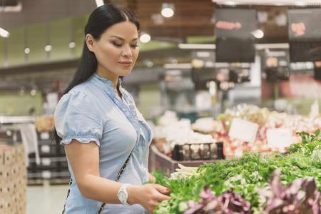 Serene female making choice of green vegetables Stock fotó