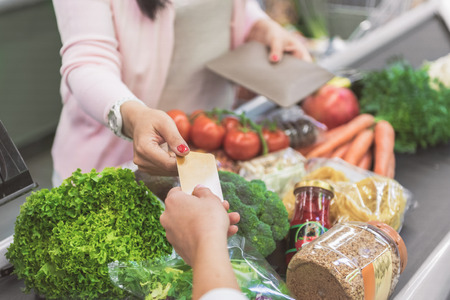 Customer giving card to supermarket worker Standard-Bild