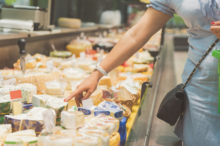 I would like this one. Close up woman hands showing on piece of appetizing cheese in supermarket 版權商用圖片