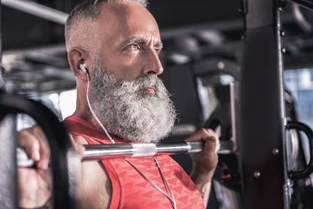 Stijlvolle zelfverzekerde volwassen mannetje geniet van sport in atletisch centrum