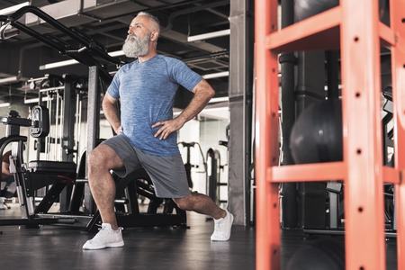Stylish old male is enjoying workout in modern gym