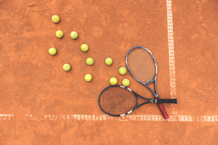 Rackets are near number of balls at covering of court. Top view. Copy space on left side