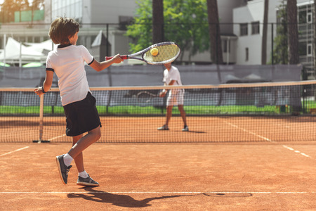 Male child playing tennis with opponent Фото со стока
