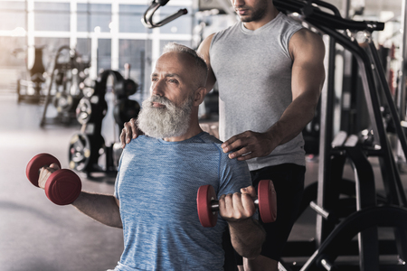 Senior sportsman is spending time in athletic center with trainer