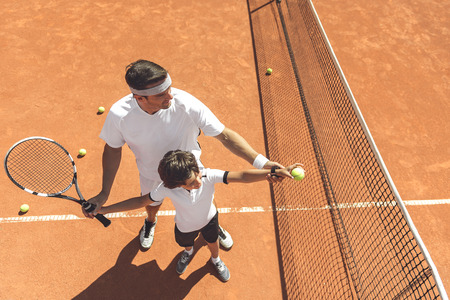 Aprendizaje de la familia para jugar al tenis Foto de archivo - 85605075
