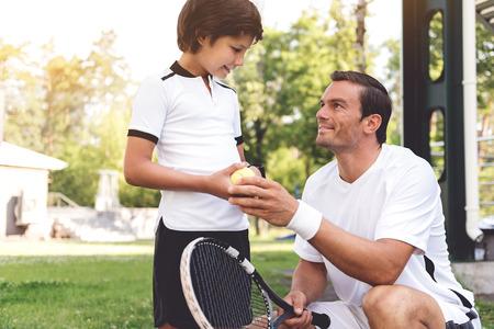 Nieuwsgierige sportieve jongen die dichtbij vader de plaats bepaalt