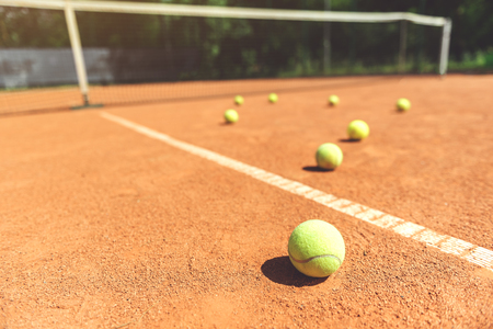 Various yellow small round balls on court
