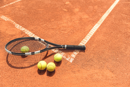 Racquet beside round objects on court