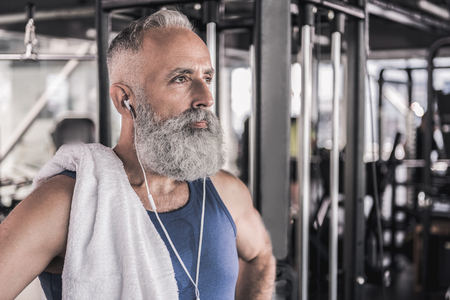 Confident stylish pensioner is thinking while standing in sport center