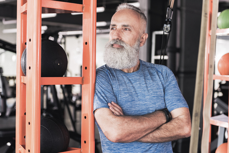 Old male with beard is resting in athletic club