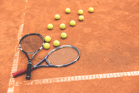 Tennis rackets locating at court near small balls. Objects are on white marks. Top view. Copy space on right side