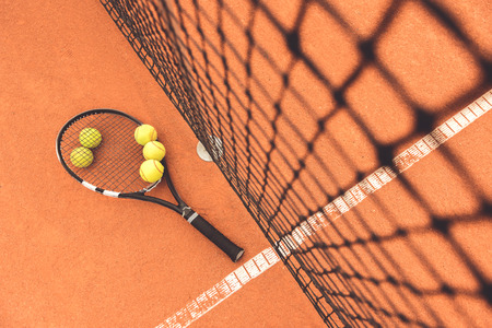 Small yellow balls are under tennis racket and above it. Equipment near grid at arena. Top view. Copy space on right side