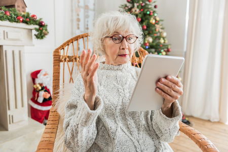 How to use. Senior woman is holding tablet and looking at screen while expressing discontent and perplexity. Christmas tree and Santa Claus are on background Stock Photo