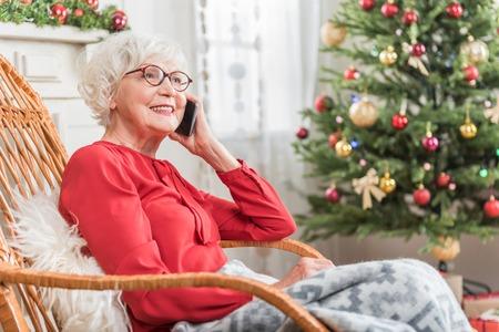 Gespräch genießen. Charmante ältere Frau spricht am Handy und drückt Glück aus. Sie sitzt im Schaukelstuhl gegen Weihnachtsbaum. Platz auf der rechten Seite kopieren Standard-Bild
