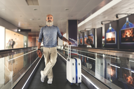 Confident mature tourist is standing on moving tape and looking ahead with kind of superiority. He has luggage. Full length portrait. Copy space on right side Stock Photo