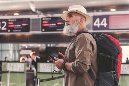 空港に立ちながら、聖書やアクセサリーを腕に持ち続ける静かなあごひげの祖父