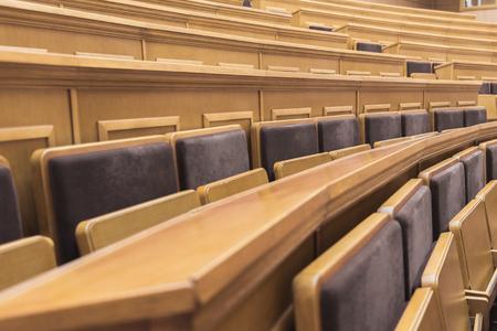 Zijaanzicht dicht omhoog van comfortabele zetels en lijsten in auditoriumruimte bij universiteit Stockfoto