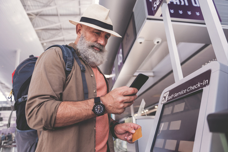 Low angle smiling unshaven pensioner typing in phone while standing near cash machine in airport Stok Fotoğraf - 85766518