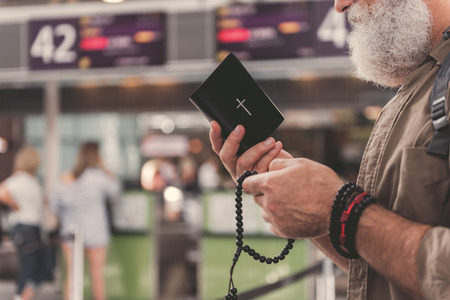 Close up old man hand holding bible and beads. He reading it. Copy space Stock Photo