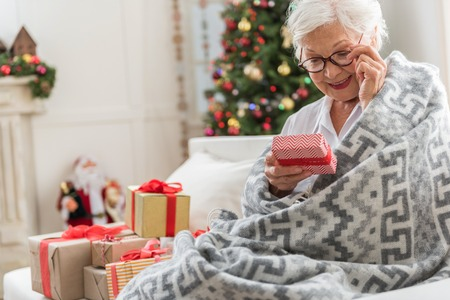 Beautiful greeting. Positive gray-haired lady is holding gift box and reading congratulation while touching her glasses and expressing gladness. Copy space in the left side