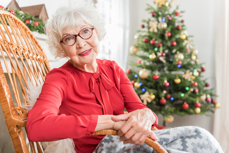 Great mood. Portrait of charming elderly woman is sitting in rocking chair and looking at camera with smile. She is resting with Christmas tree on background. Copy space in the right side Standard-Bild