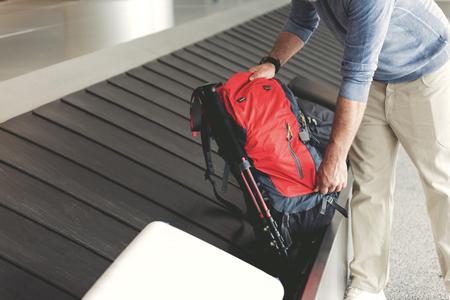 男は荷物テープの近くに立って、赤いバックパックを取るします。男性の手で袋のクローズ アップ。左側にコピー スペース