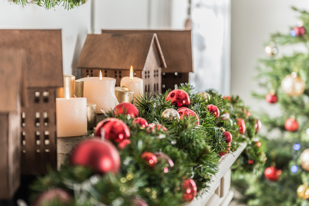 Festive decorations. Close-up of Christmas fir branches with red balls and burning candles with toy houses are decorating fireplace