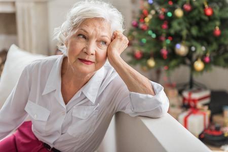 Recuerdos nostálgicos. La señora de edad melancólica está mirando a un lado pensativa mientras se apoya en el codo y se toca la cara. Ella está descansando en el sofá con el árbol de Navidad y cajas de regalo en el fondo