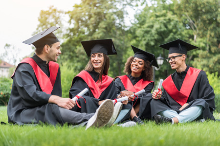 Happy young students relaxing on lawn in graduation clothes