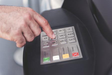 Sluit omhoog het oude mensenhand typen op knopen van contant geldmachine Stockfoto