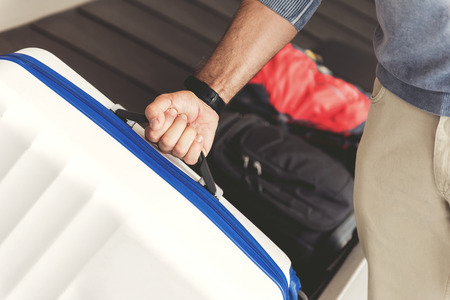 Tourist is taking his luggage from baggage tape in terminal. Close up of male hand holding handle of bag